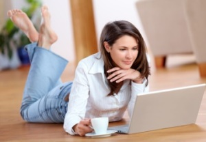 Young woman with laptop and a cup of coffee on the floor